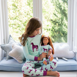 Girl and doll matching unicorn pjs